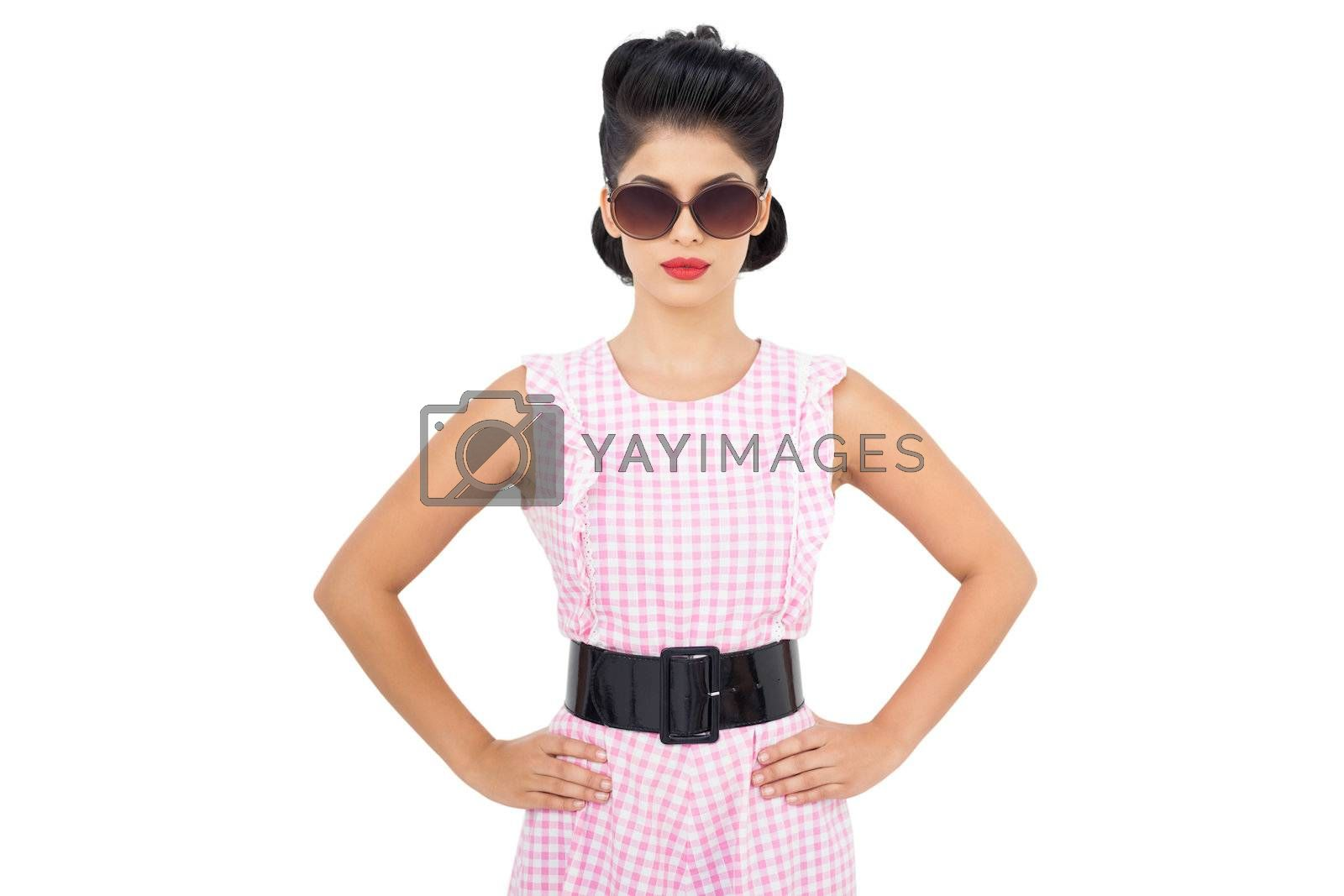 Unsmiling black hair model wearing glasses and posing hands on the hips by Wavebreakmedia
