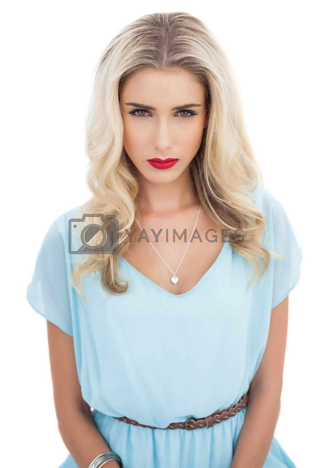 Puzzled blonde model in blue dress looking at camera by Wavebreakmedia