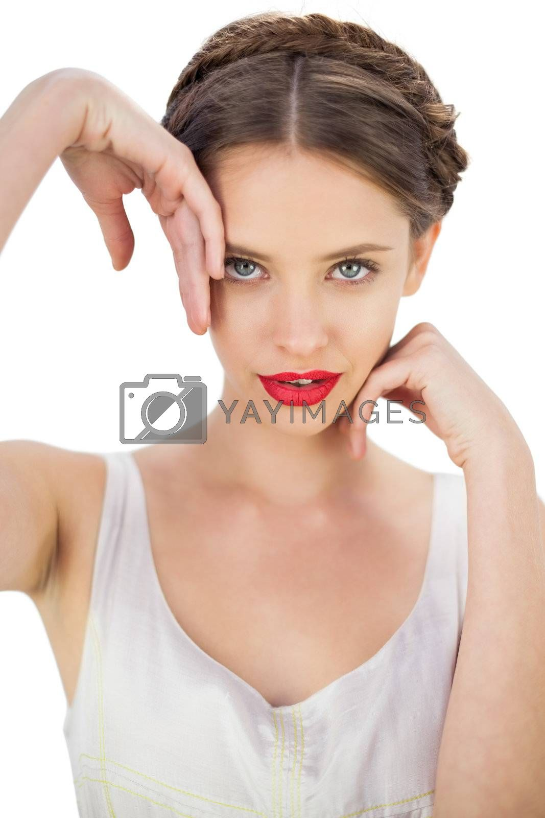 Smiling model in white dress posing touching her temple and her cheek by Wavebreakmedia