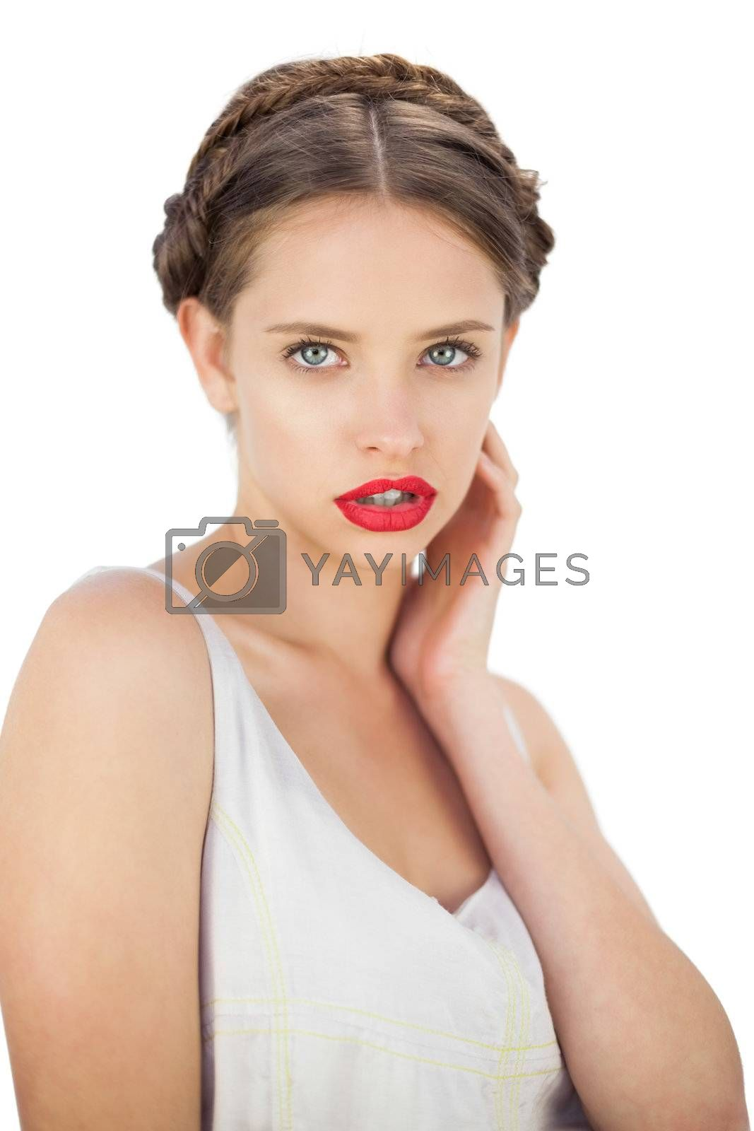 Pensive model in white dress posing withhand on her cheek by Wavebreakmedia