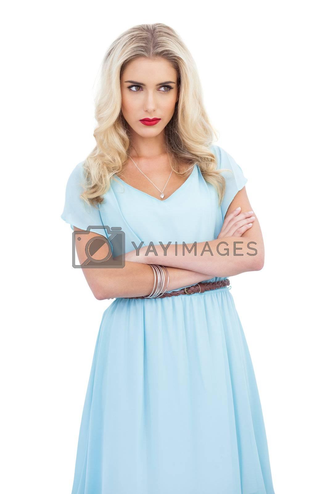Thoughtful blonde model in blue dress posing crossed arms by Wavebreakmedia