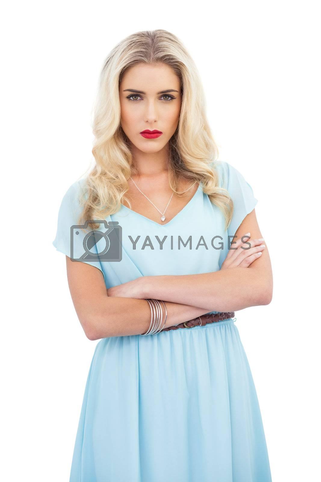 Severe blonde model in blue dress posing crossed arms by Wavebreakmedia