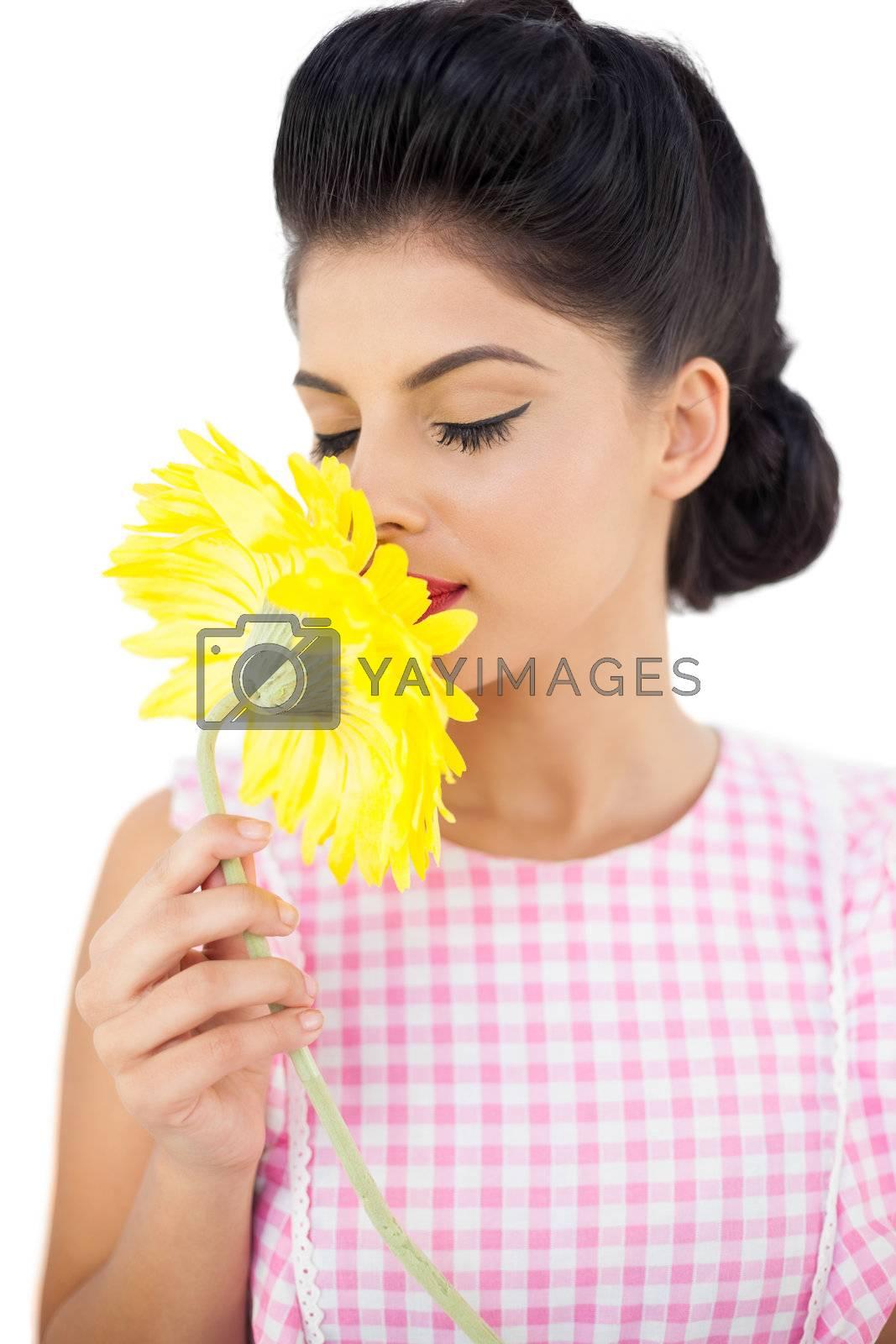 Gorgeous black hair model smelling a flower by Wavebreakmedia