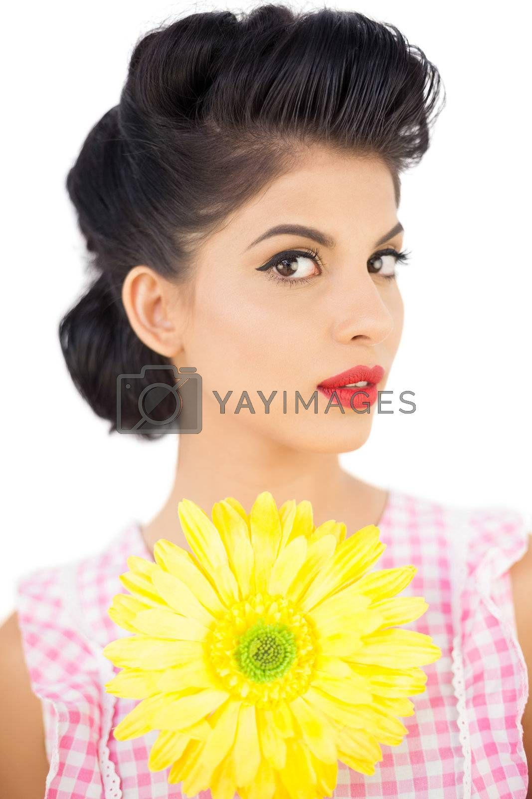 Thoughtful black hair model holding a flower and looking  by Wavebreakmedia