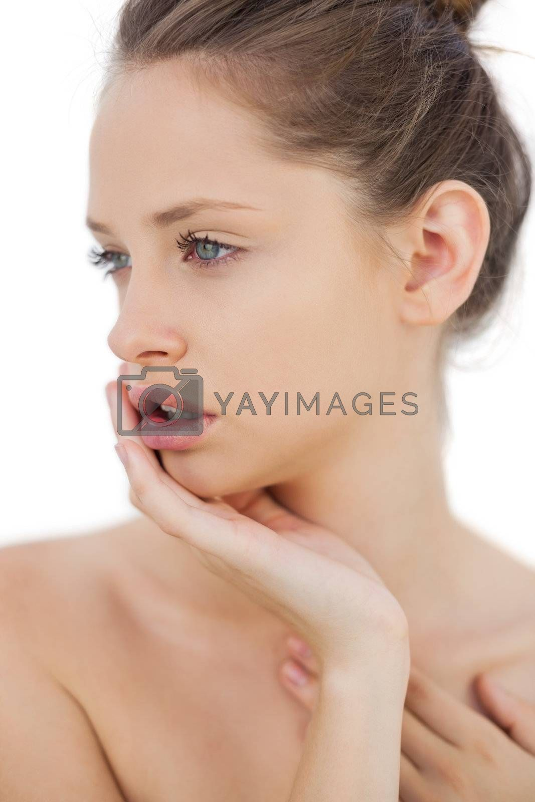 Unsmiling brunette model posing holding her head by Wavebreakmedia