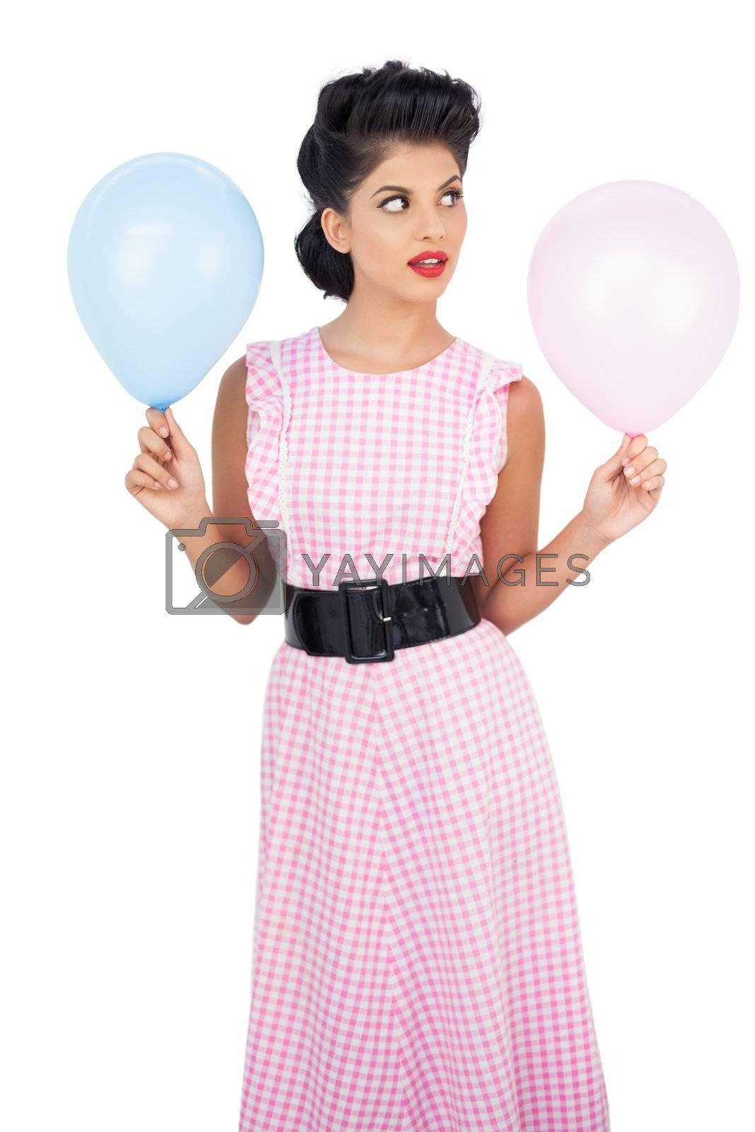 Thinking black hair model holding balloons by Wavebreakmedia
