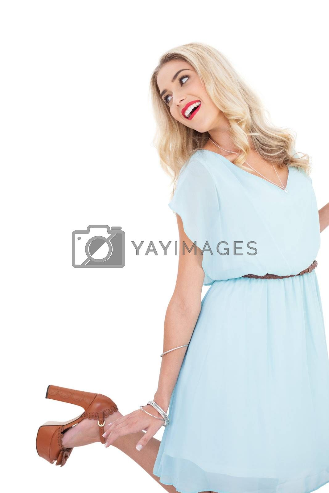 Smiling blonde model in blue dress posing and jumping by Wavebreakmedia