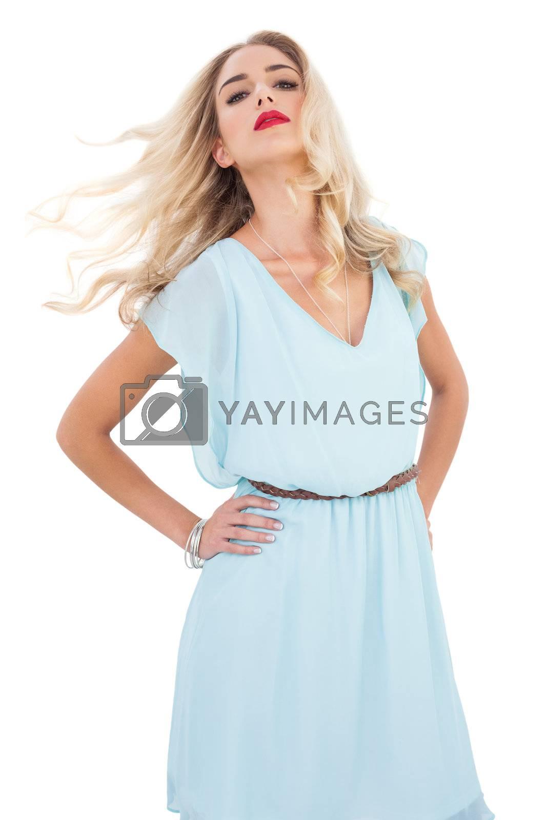 Attractive blonde model in blue dress posing shaking her hair by Wavebreakmedia