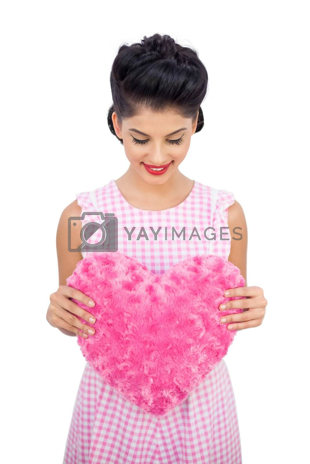 Pleased black hair model holding a pink heart shaped pillow by Wavebreakmedia
