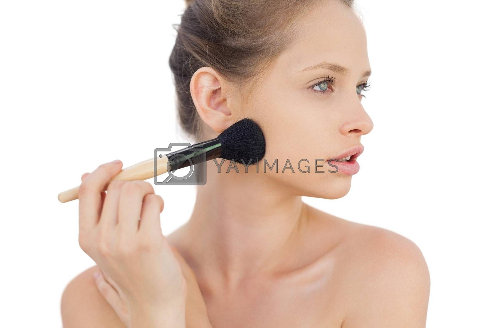 Thoughtful brunette model applying powder on her cheek by Wavebreakmedia