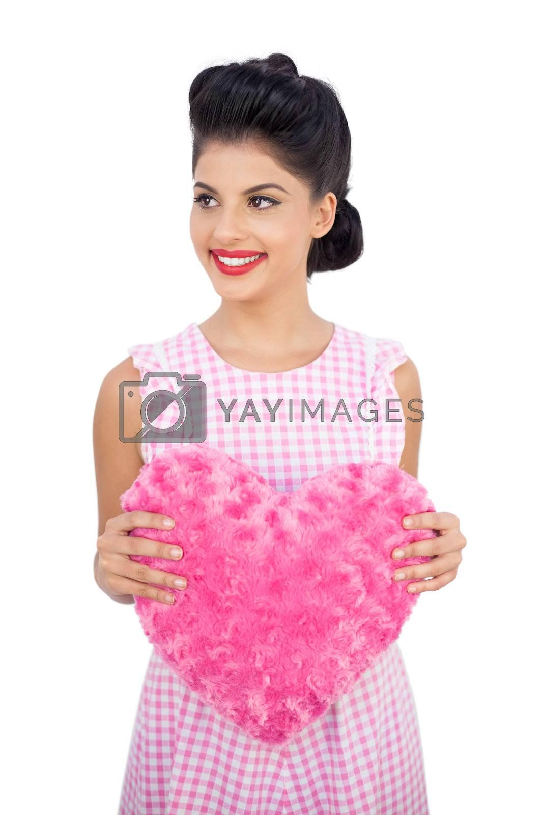 Joyful black hair model holding a pink heart shaped pillow by Wavebreakmedia