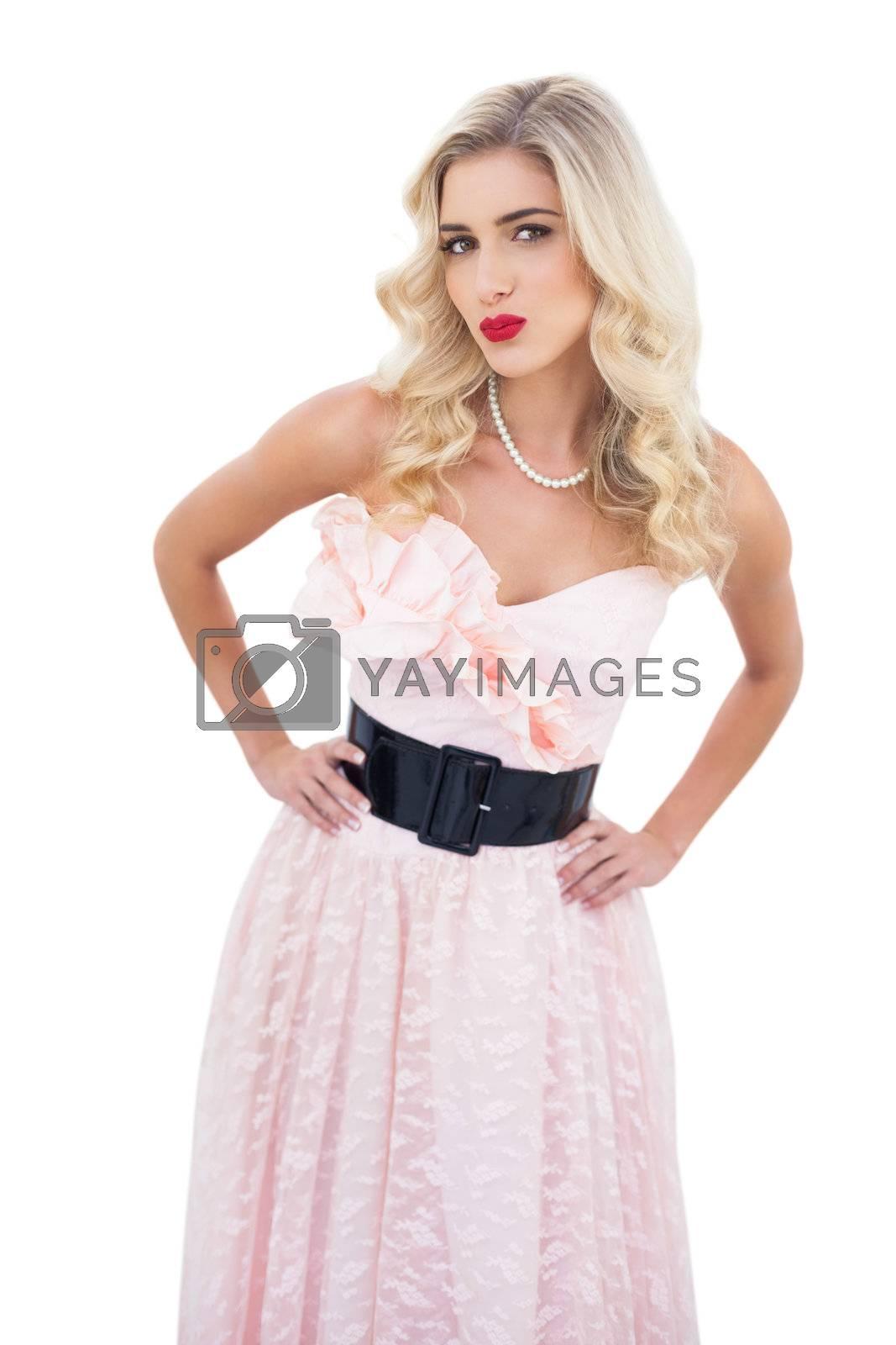 Seductive blonde model in pink dress posing hands on the hips by Wavebreakmedia