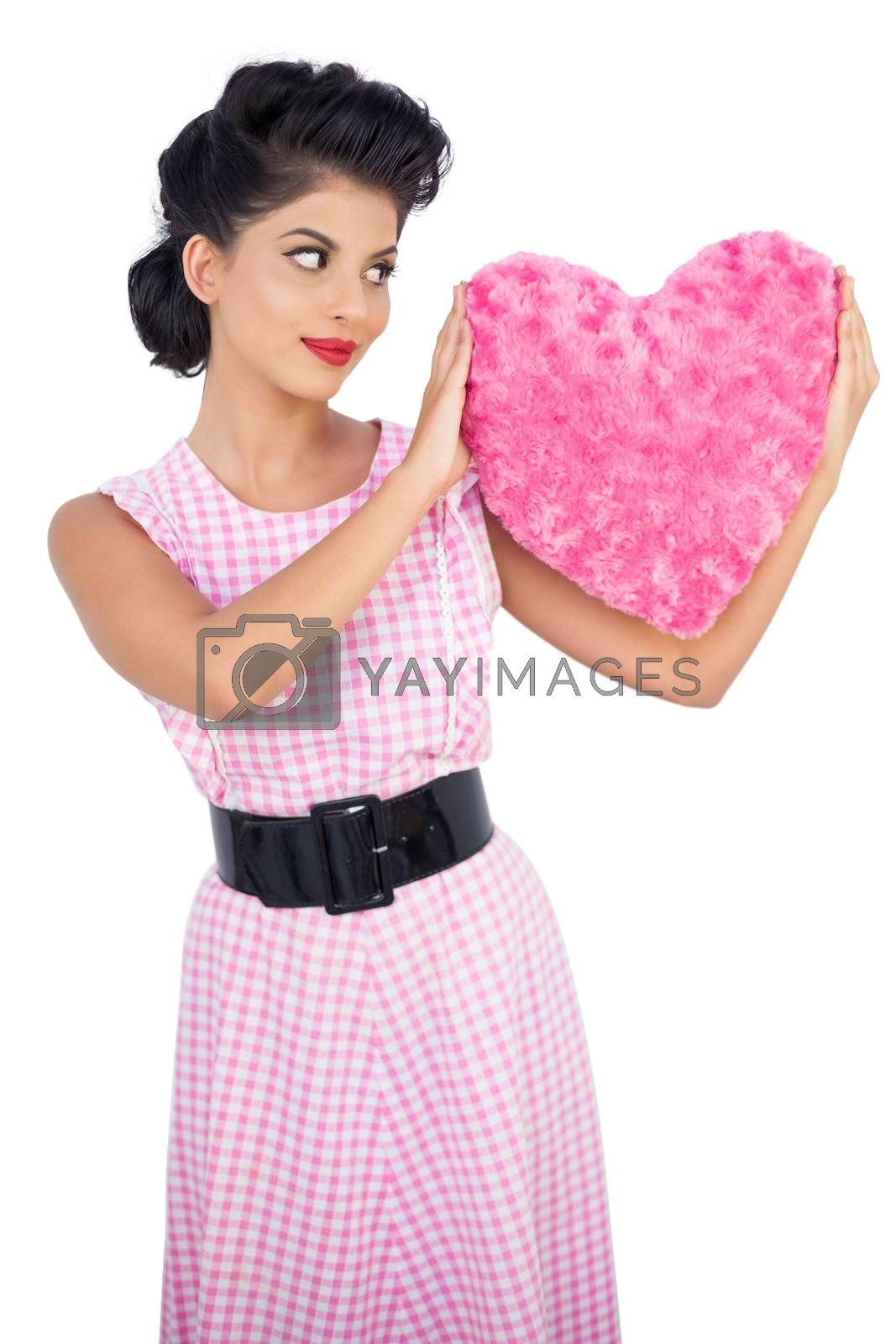 Stylish black hair model holding a pink heart shaped pillow by Wavebreakmedia