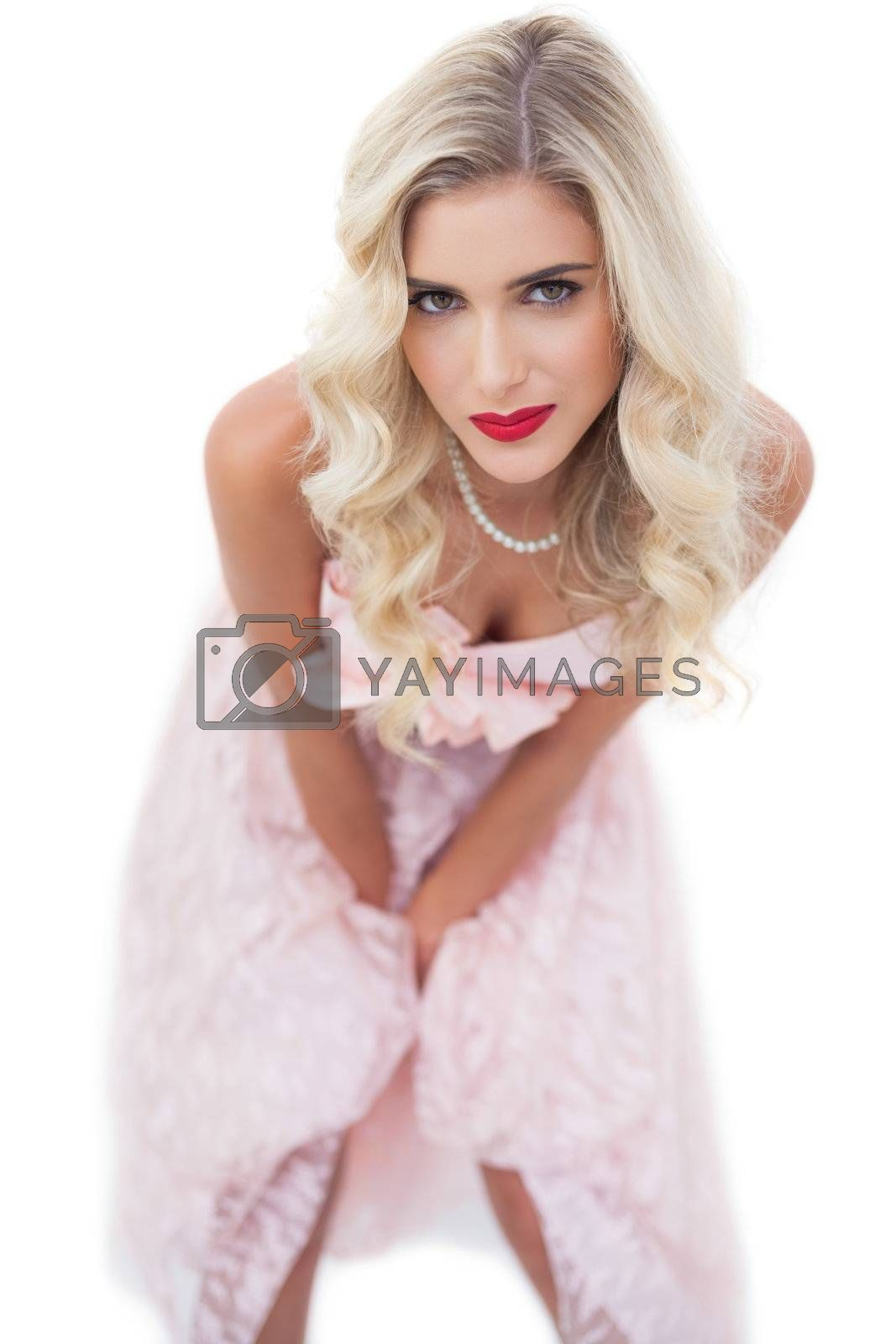 Pretty blonde model in pink dress posing hands on the thighs by Wavebreakmedia