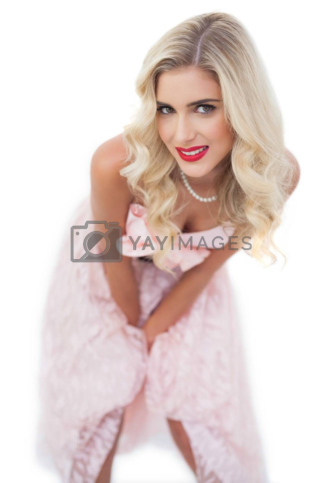 Smiling blonde model in pink dress posing hands on the thighs by Wavebreakmedia