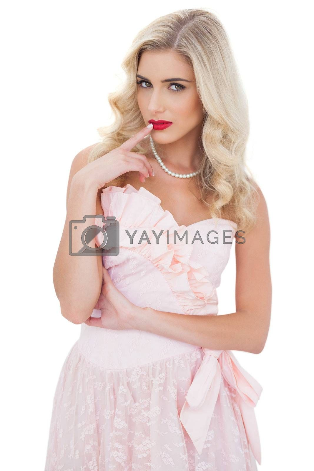Contemplative blonde model in pink dress posing a finger on the mouth by Wavebreakmedia