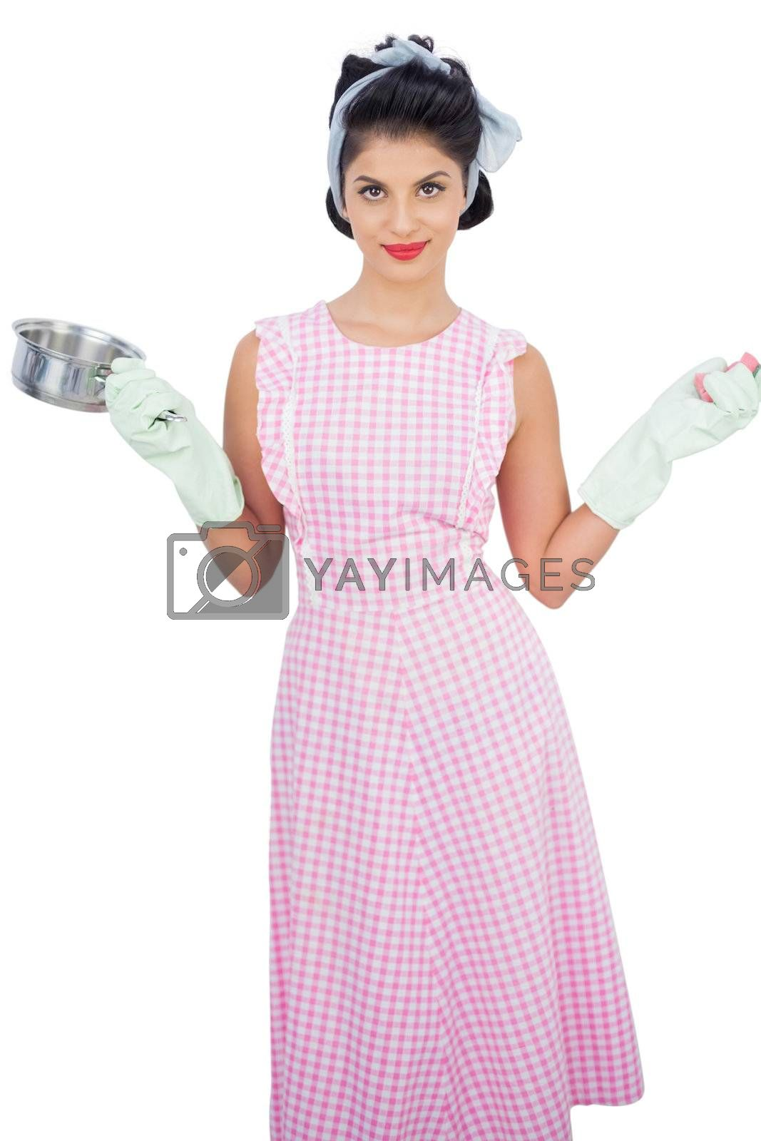 Smiling black hair model holding a pan and wearing rubber gloves by Wavebreakmedia