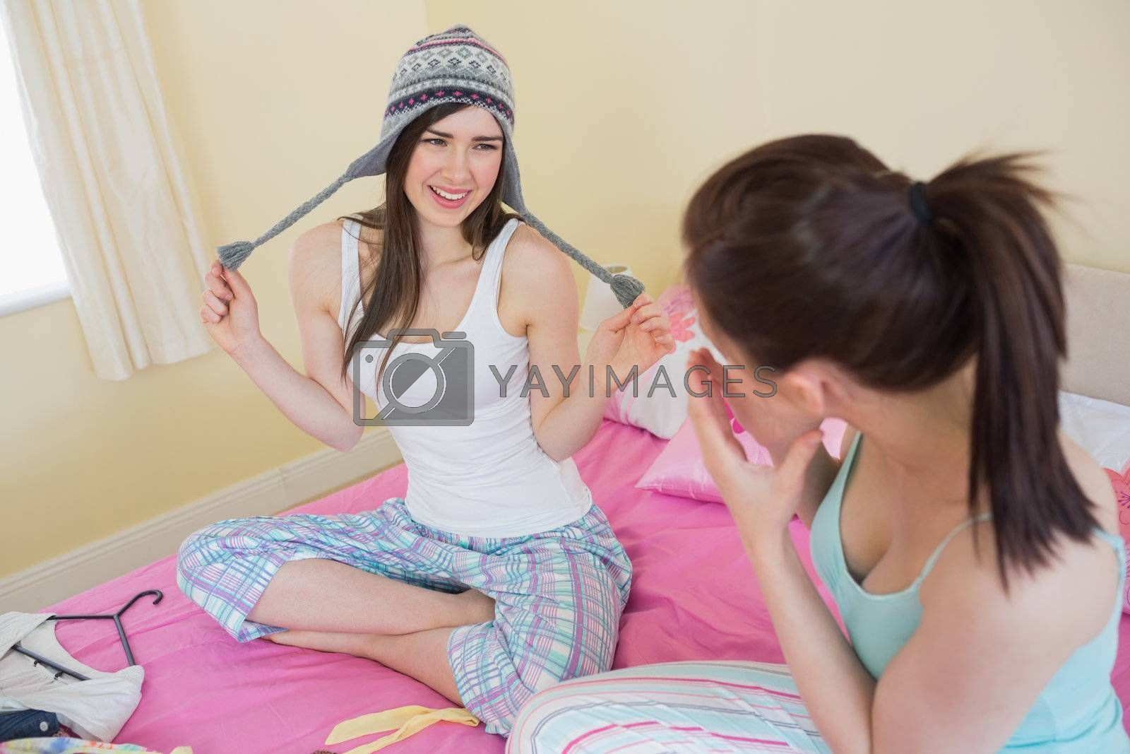 Funny girl trying on wool hat for her laughing friend by Wavebreakmedia