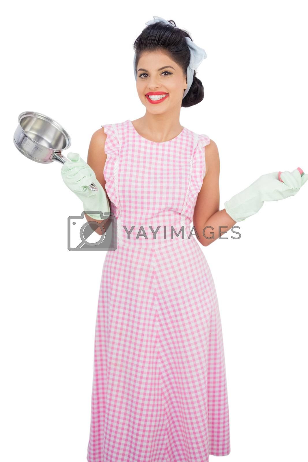 Joyful black hair model holding a pan and wearing rubber gloves by Wavebreakmedia
