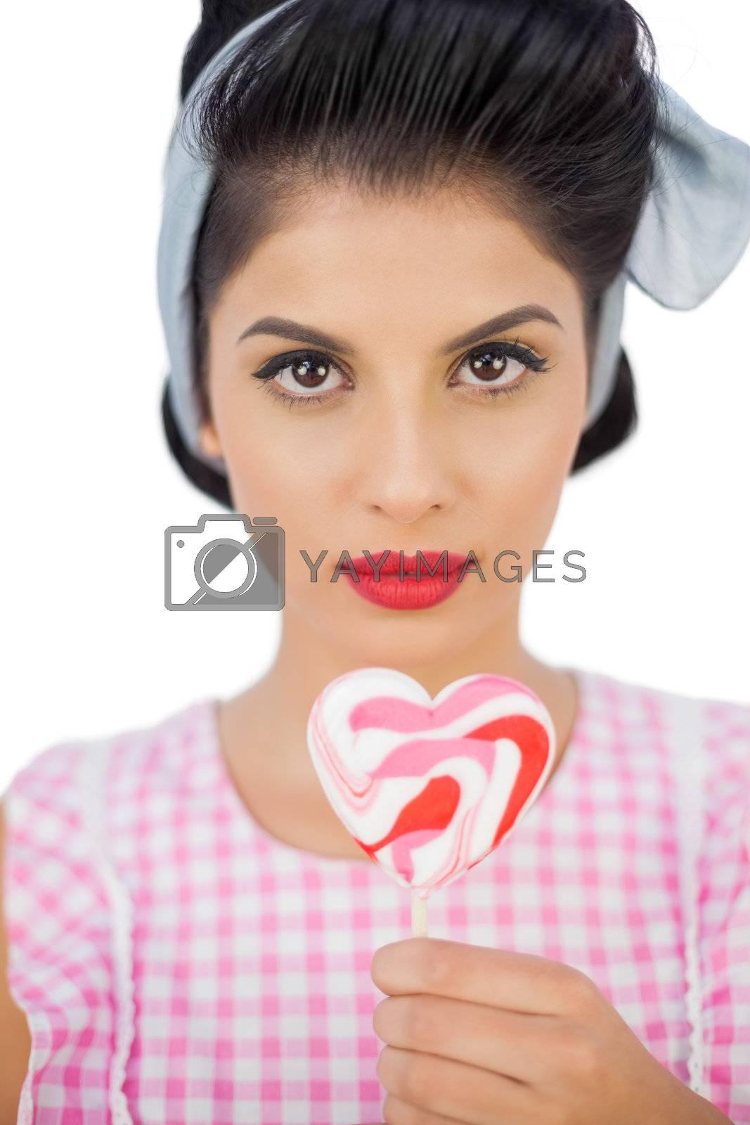 Serious black hair model holding a heart shaped lollipop by Wavebreakmedia