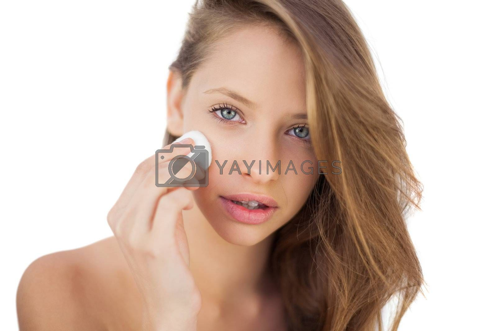 Calm brunette model rubbing her face with cream by Wavebreakmedia