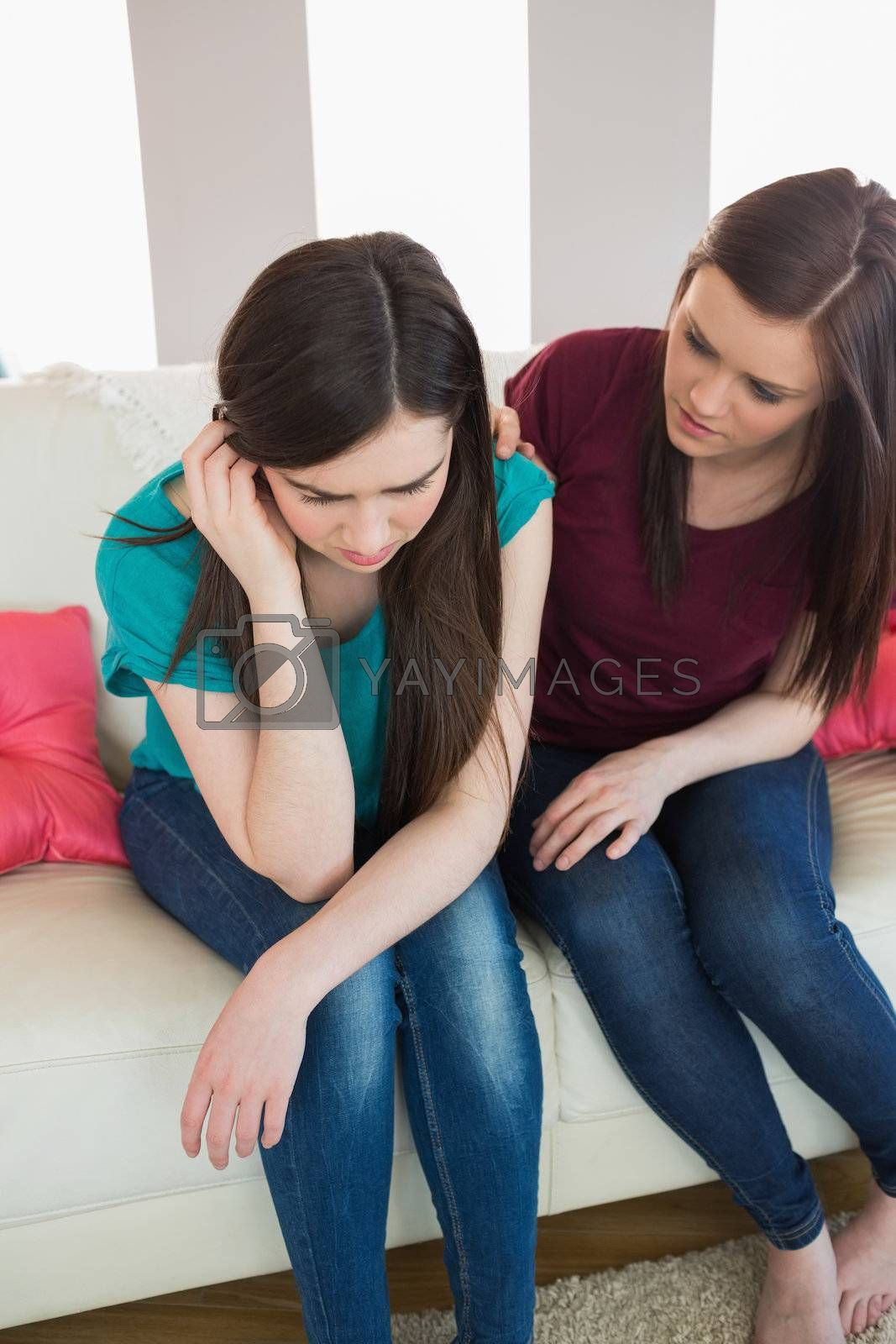 Girl comforting her upset crying friend on the couch by Wavebreakmedia