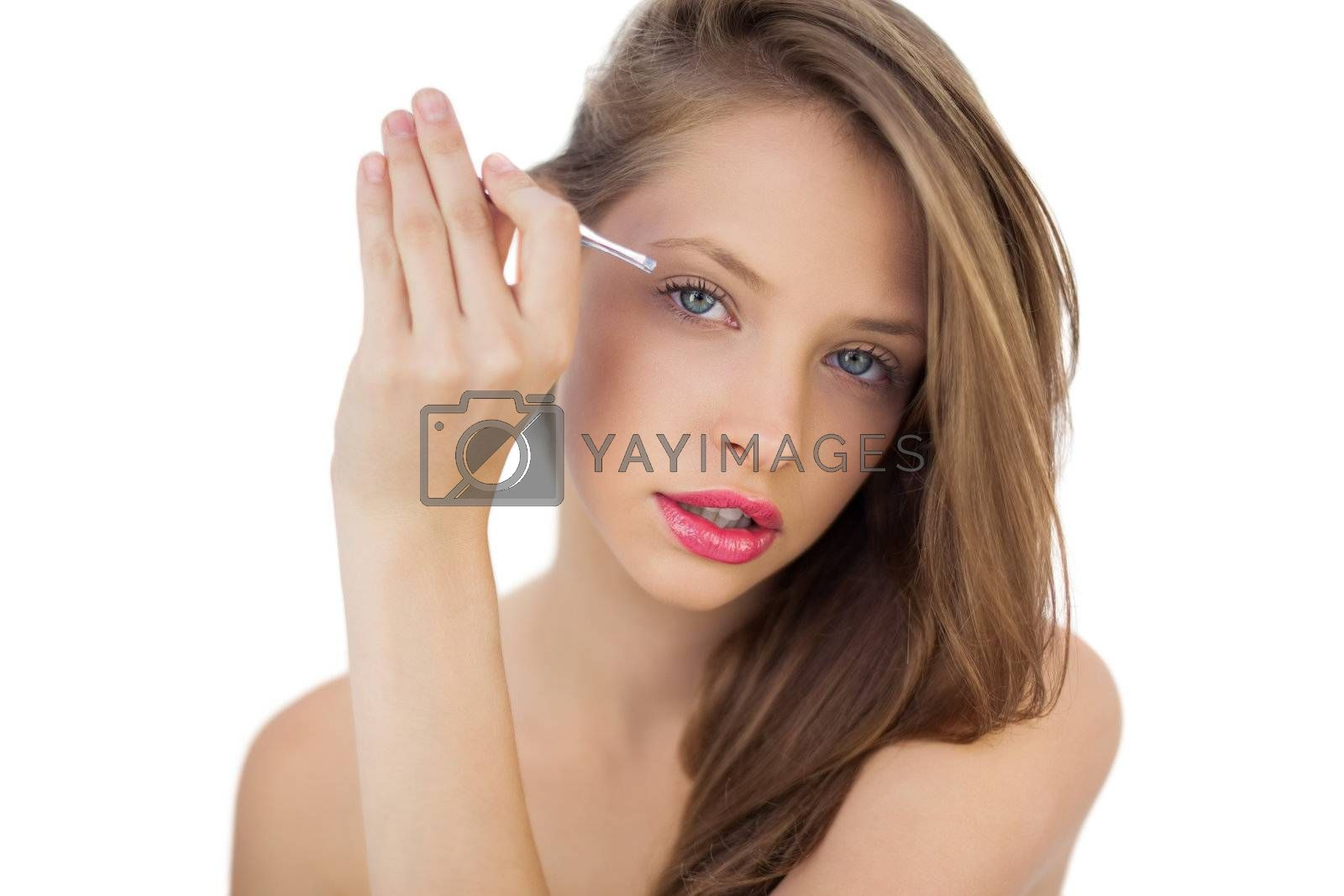 Focused brunette model plucking her eyebrows by Wavebreakmedia