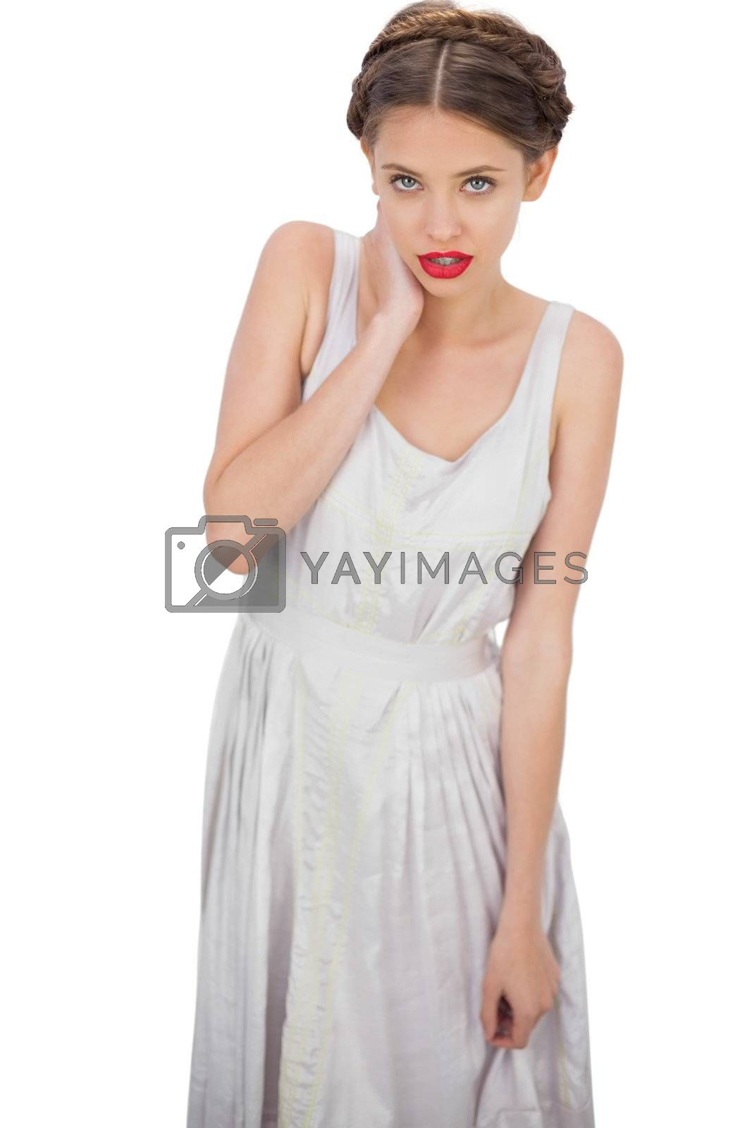 Embarrassed model in white dress posing hand on the neck by Wavebreakmedia