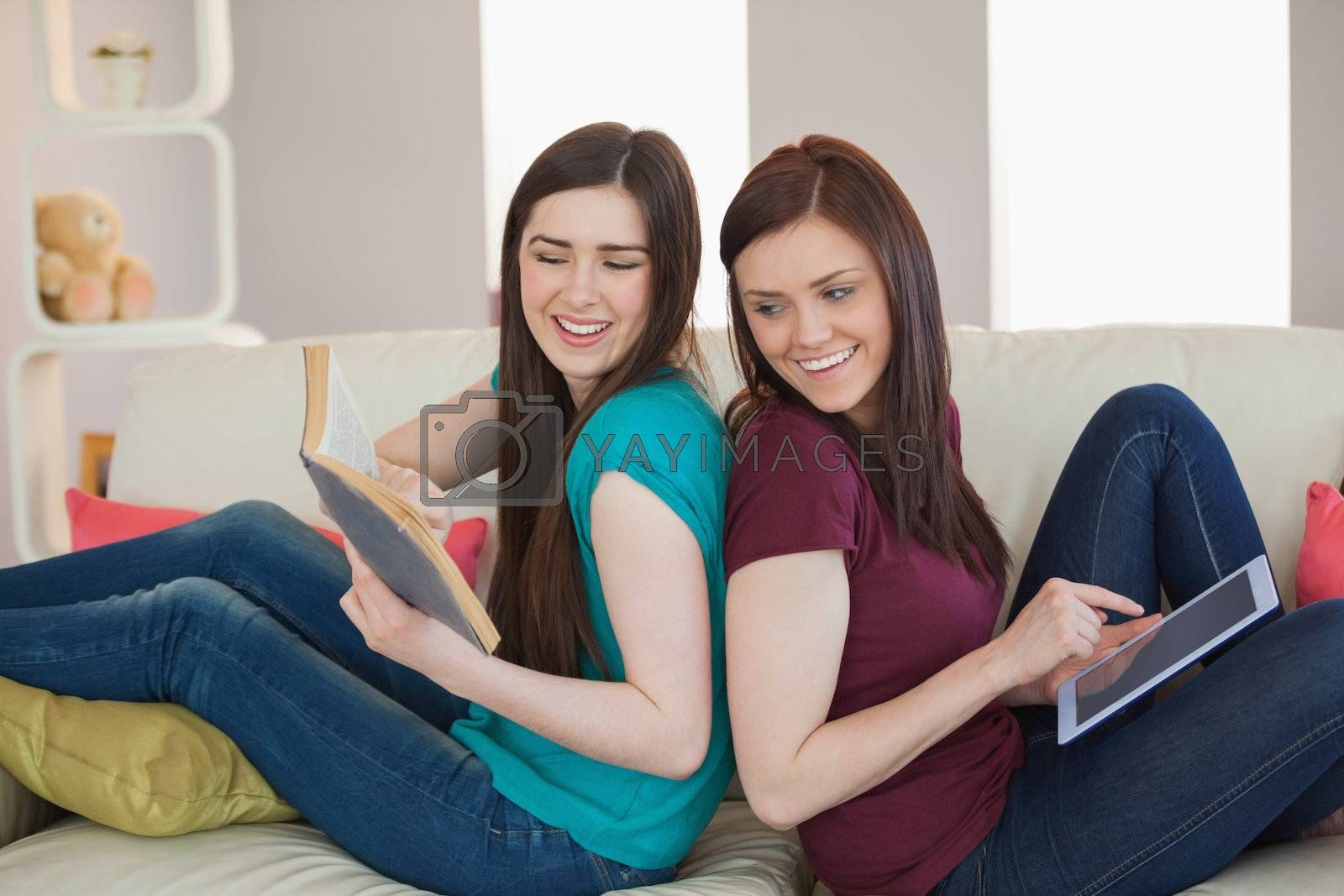 Girl showing her friend her book on the sofa by Wavebreakmedia