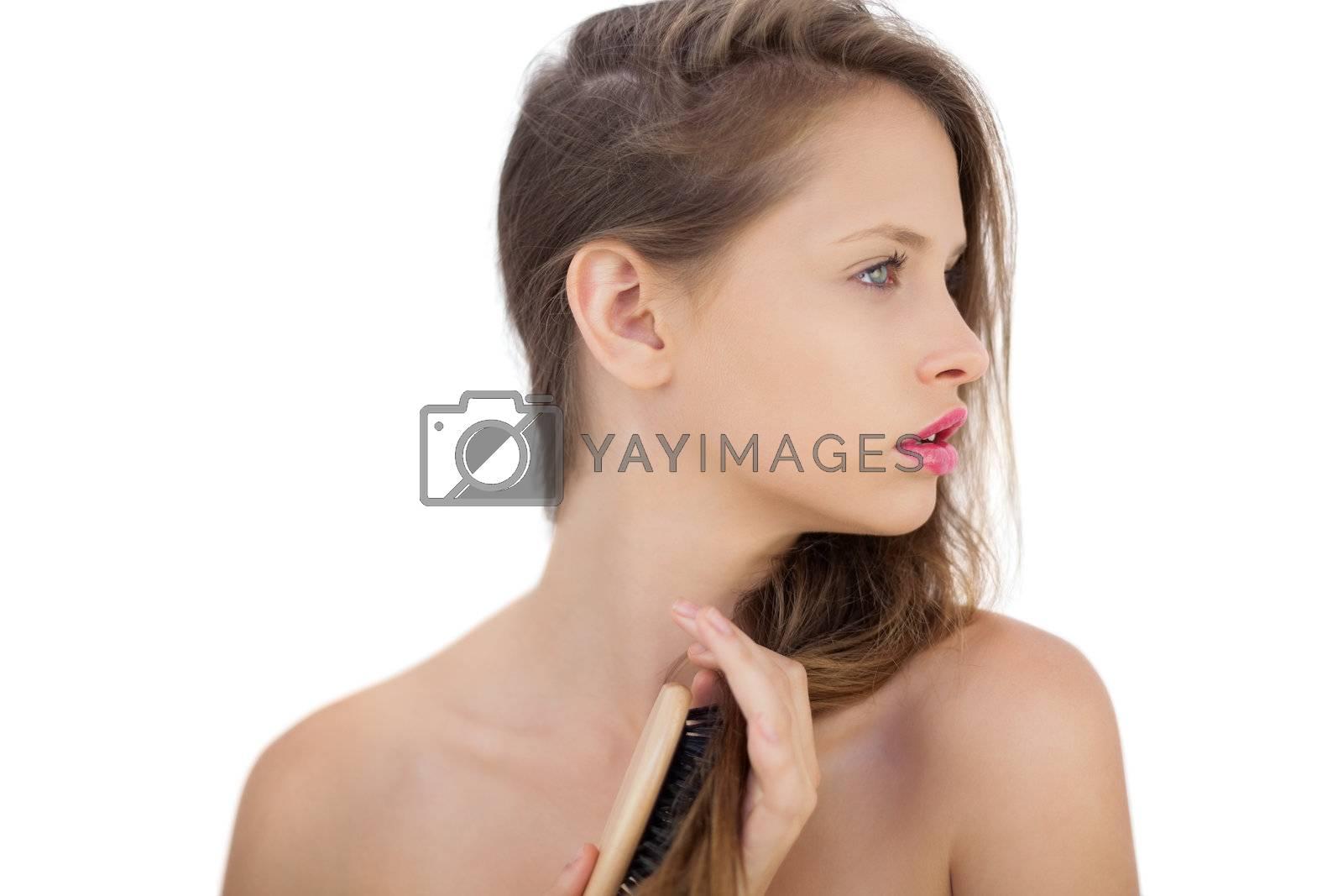 Pensive brunette model brushing her hair by Wavebreakmedia