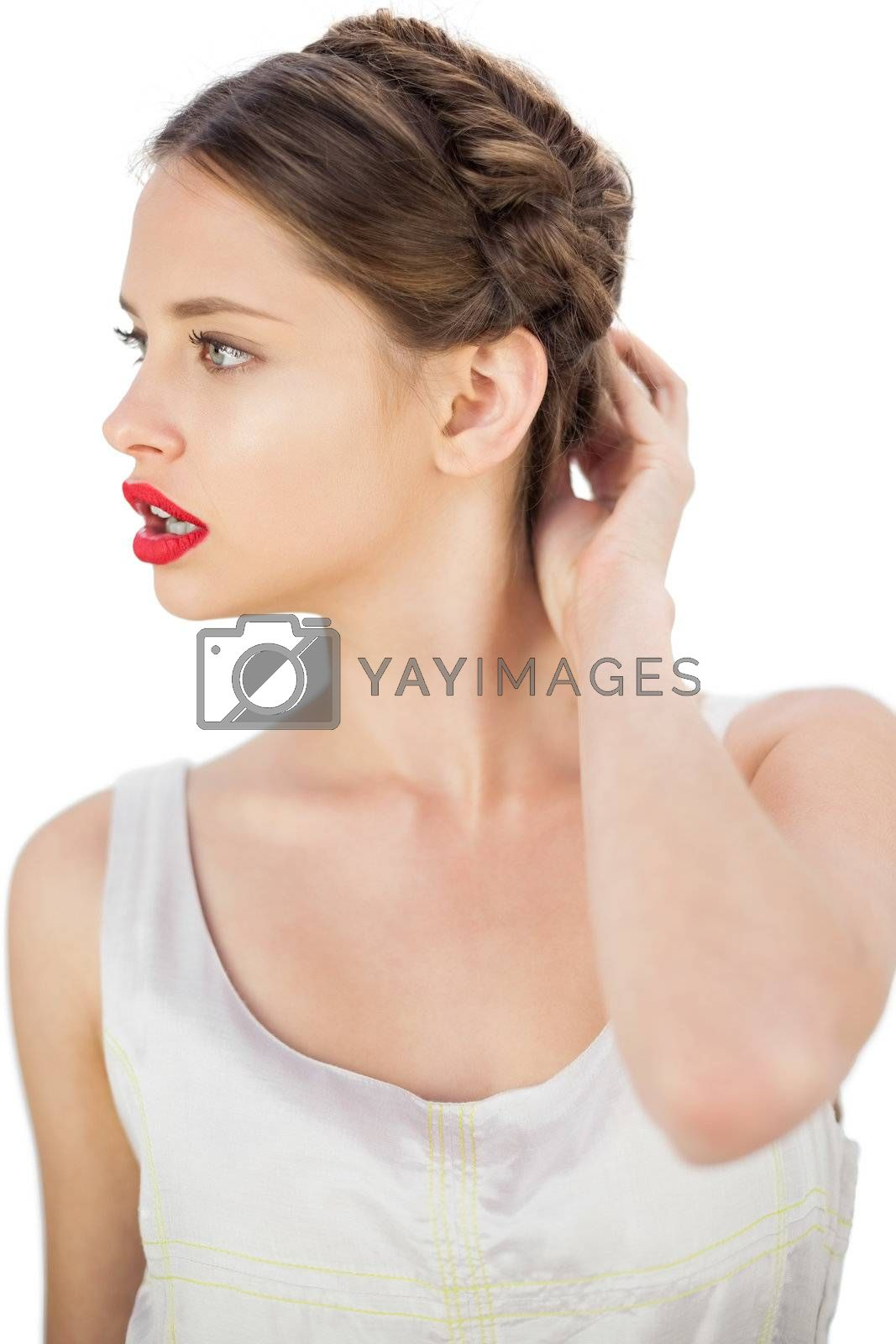 Puzzled model in white dress touching her hair and looking away by Wavebreakmedia