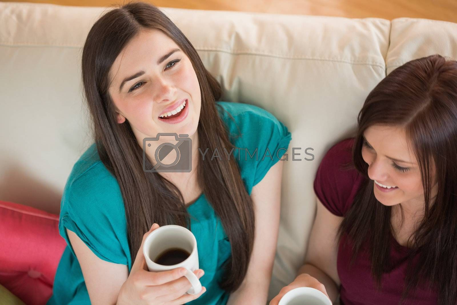 Two laughing friends having coffee on the couch by Wavebreakmedia