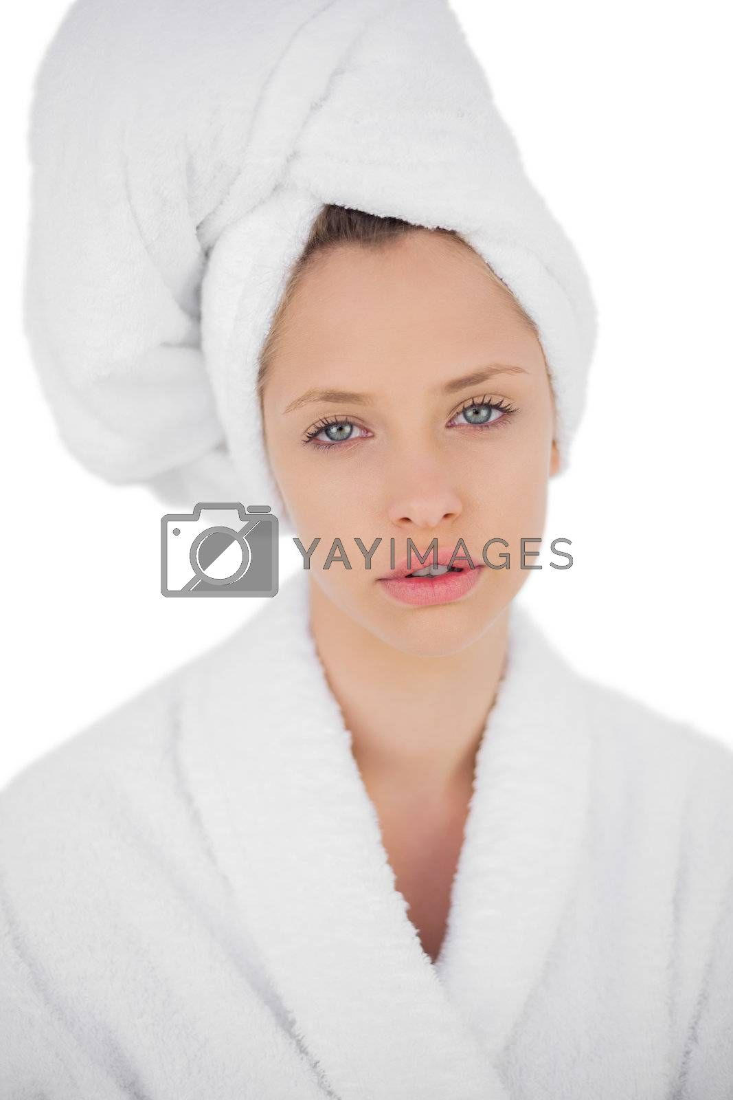Thinking brunette in bathrobe looking at camera by Wavebreakmedia