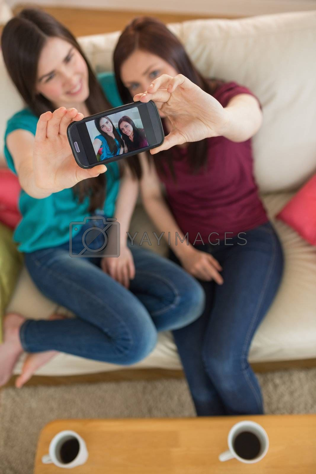 Two friends on the couch taking a selfie with smartphone by Wavebreakmedia