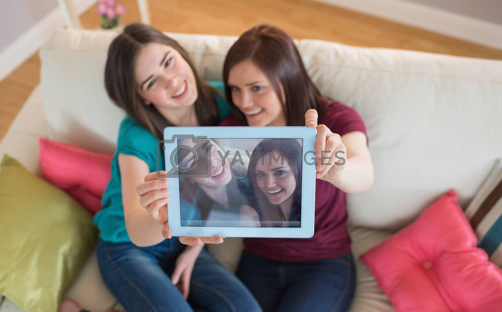 Two smiling friends on the couch taking a selfie with tablet pc by Wavebreakmedia