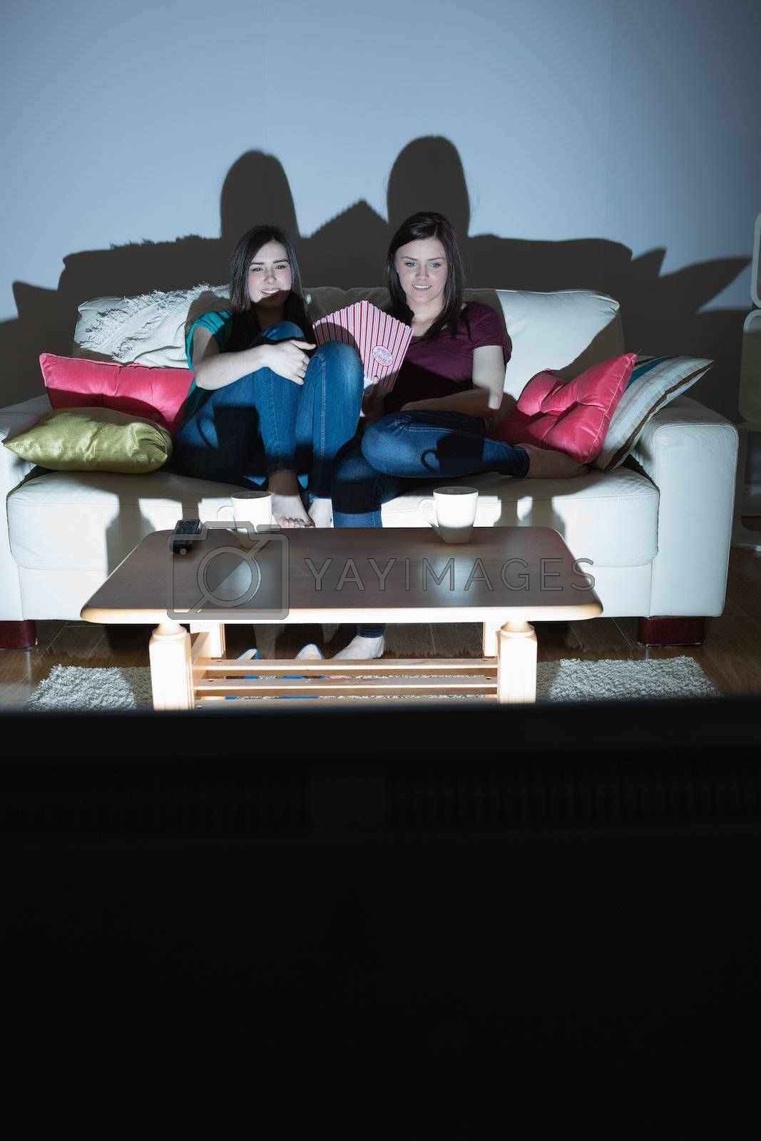Two happy friends on the couch watching tv together in the dark by Wavebreakmedia