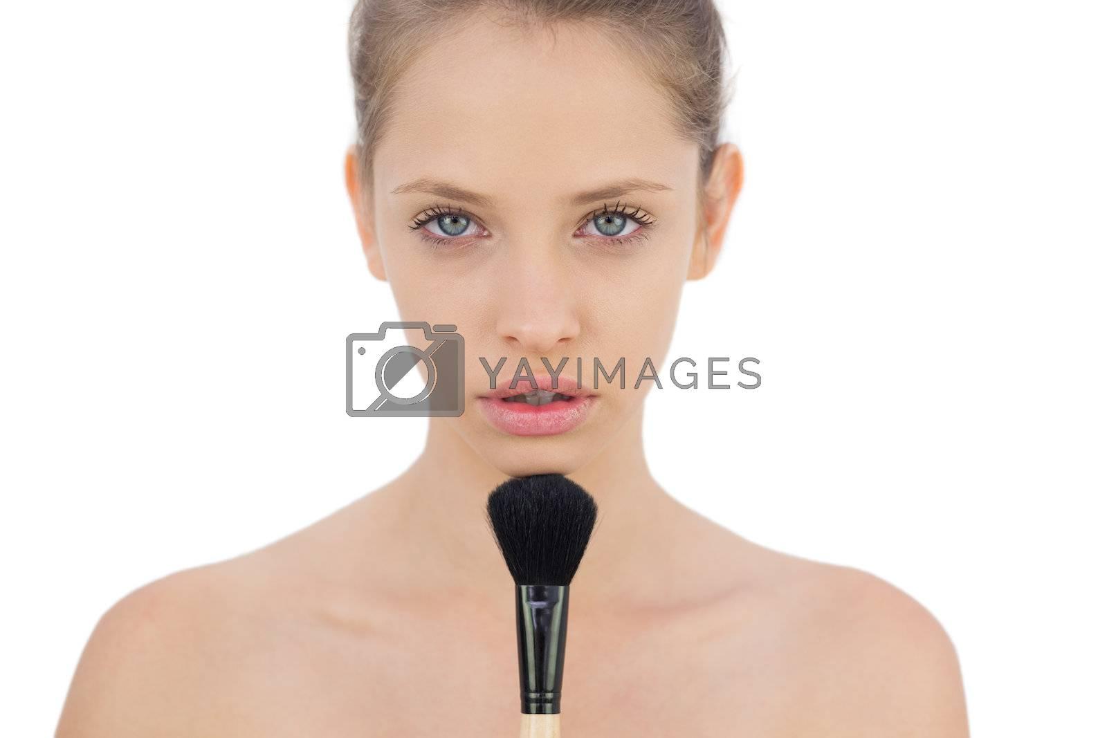 Unsmiling brunette model applying powder on her chin by Wavebreakmedia