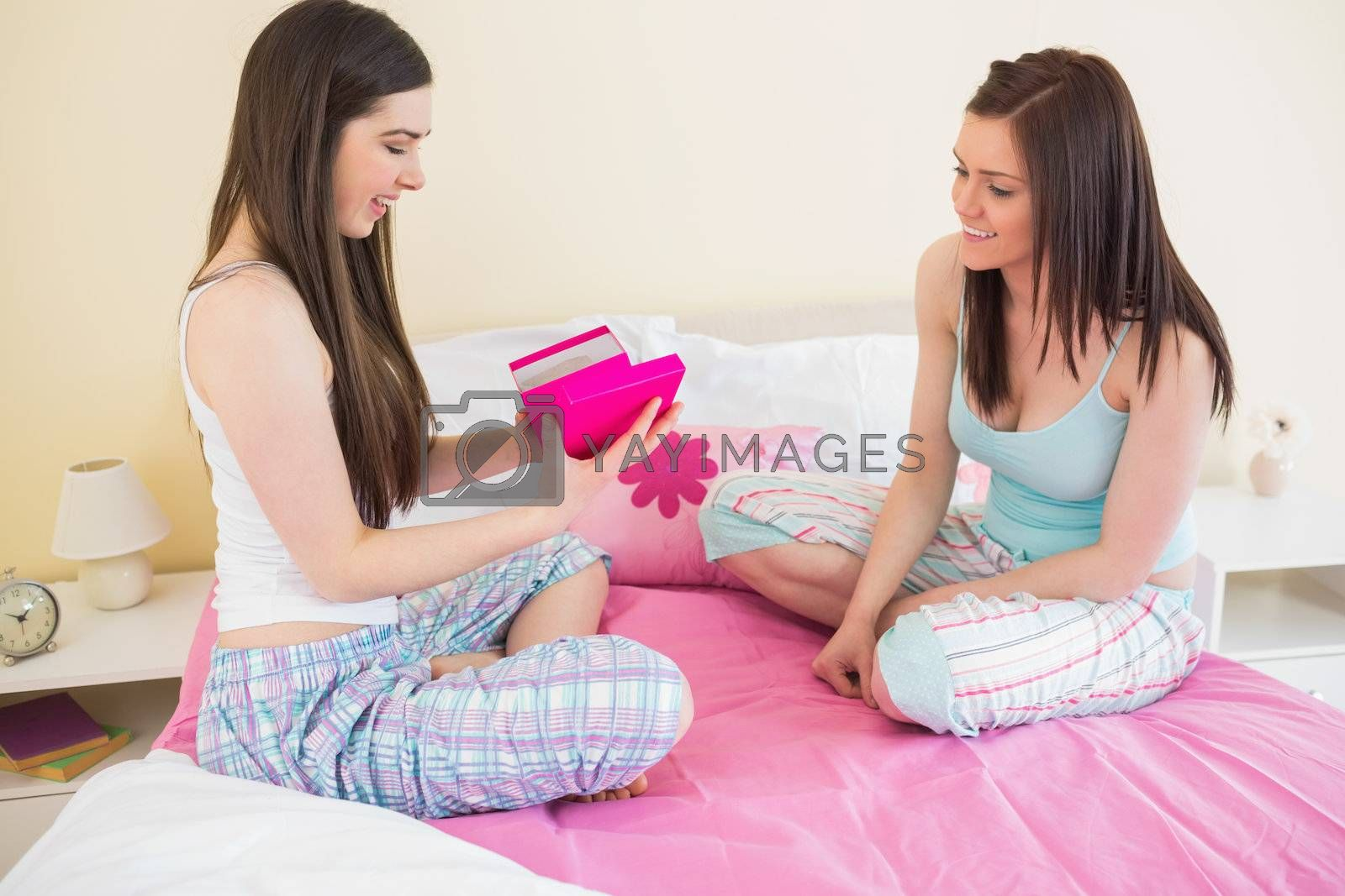Happy girl in pajamas opening a present from her friend by Wavebreakmedia