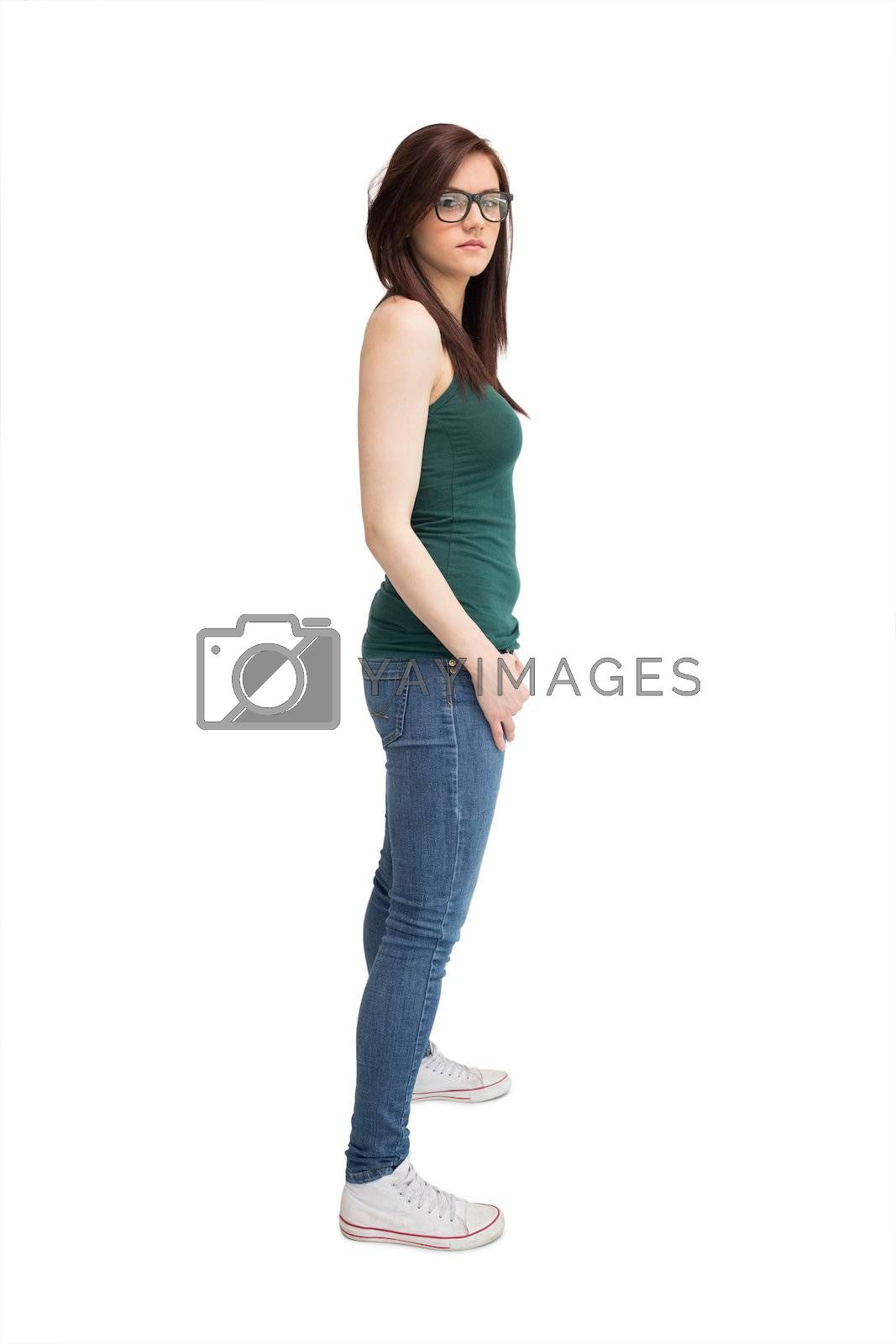 Unsmiling young woman with glasses posing by Wavebreakmedia