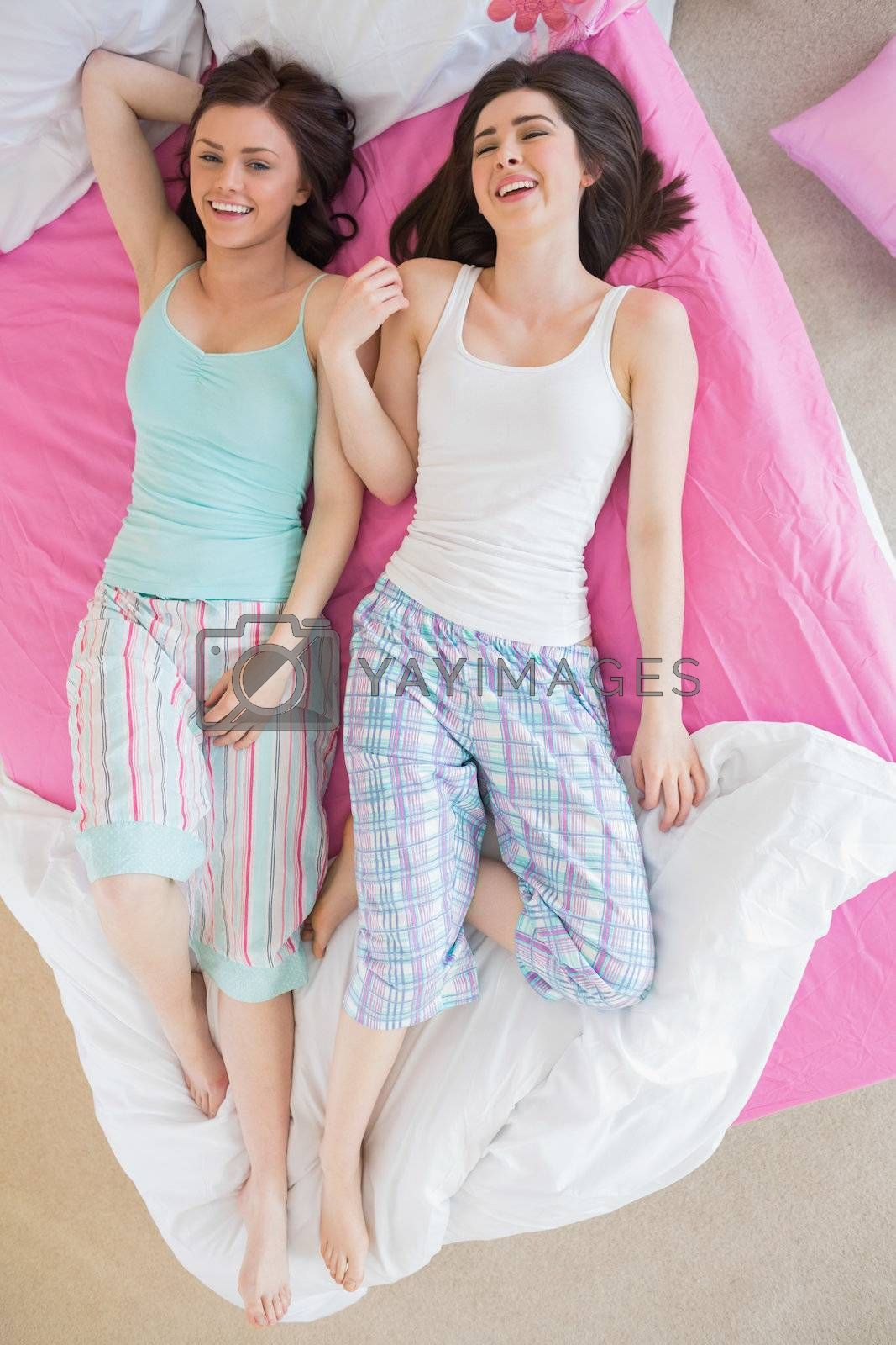 Close friends in pajamas lying on bed and laughing by Wavebreakmedia