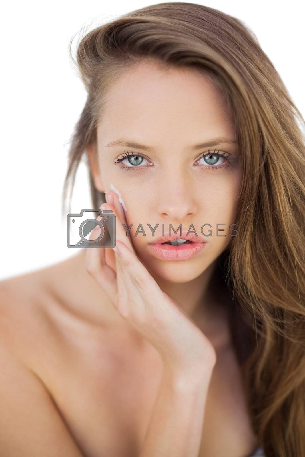 Unsmiling brunette model rubbing her cheek with cream by Wavebreakmedia
