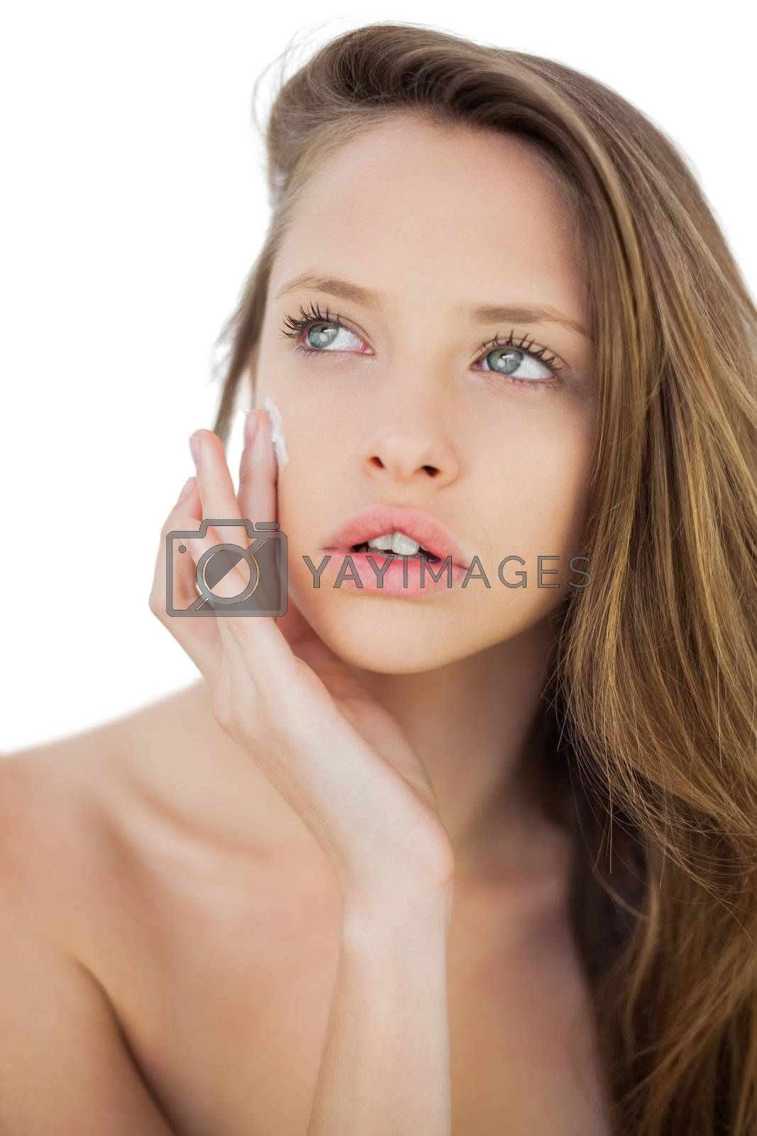 Concentrated brunette model rubbing her cheek with cream by Wavebreakmedia
