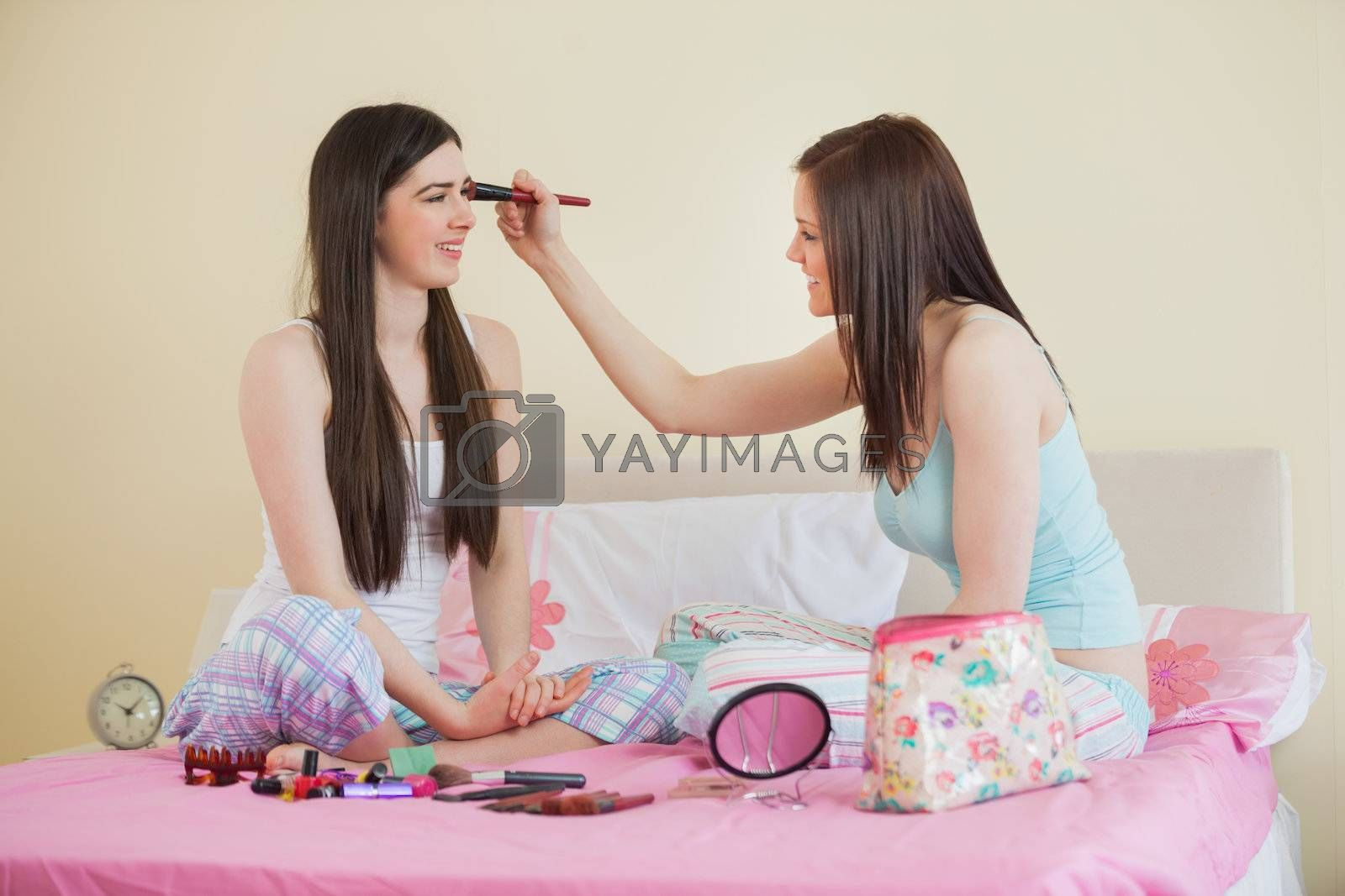 Smiling girl giving her friend a makeover at sleepover by Wavebreakmedia