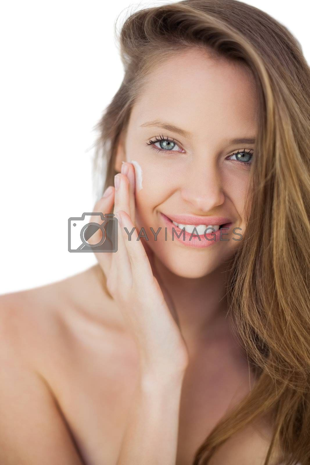 Smiling brunette model rubbing her cheek with cream by Wavebreakmedia