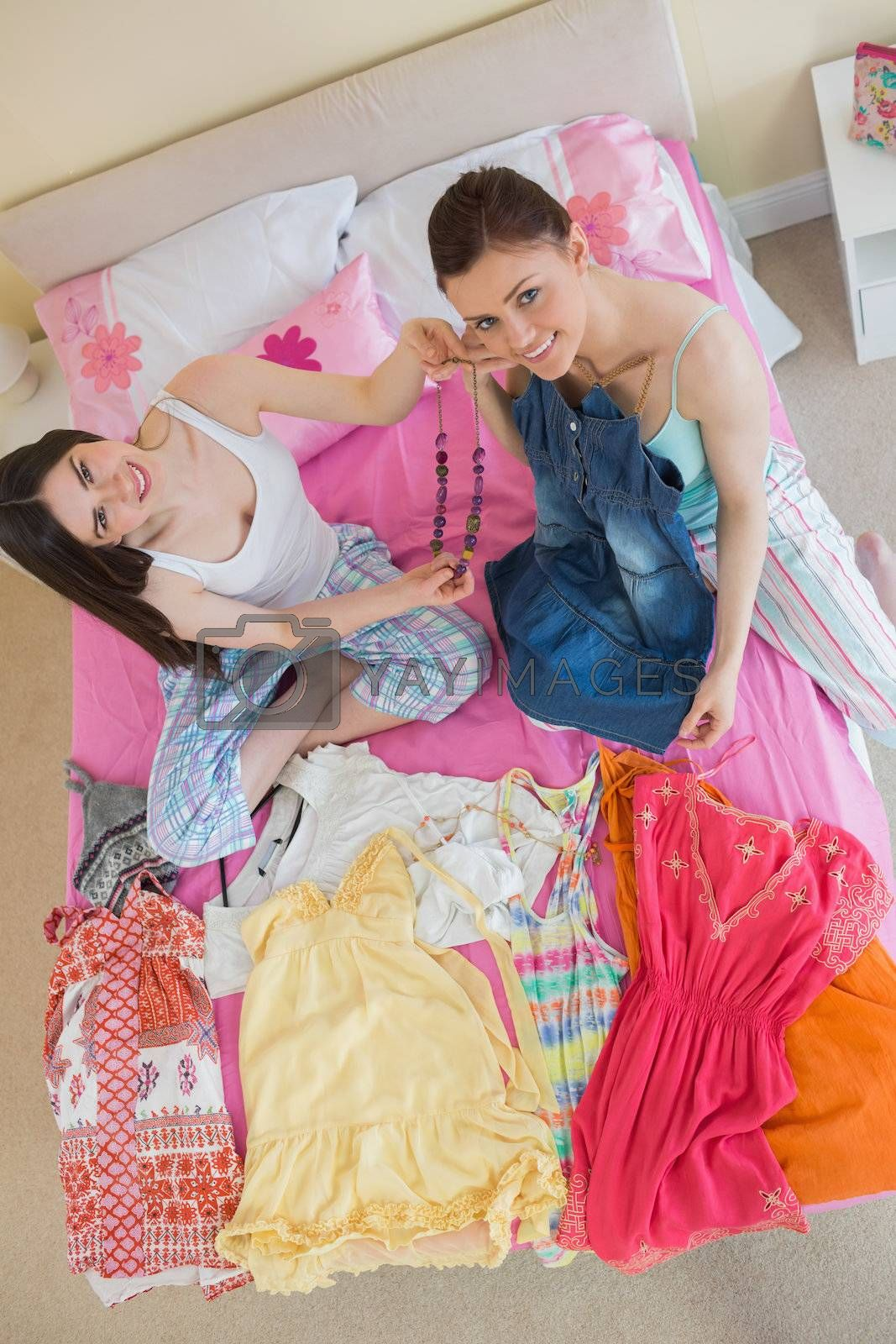 Cute girls making an outfit and looking at camera at sleepover by Wavebreakmedia