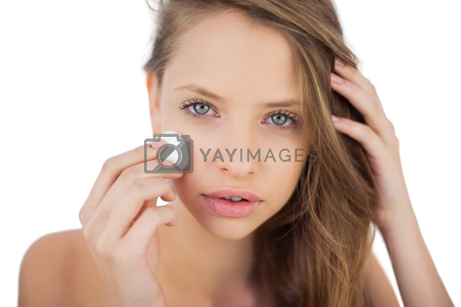 Attentive brunette model rubbing her face with cream by Wavebreakmedia