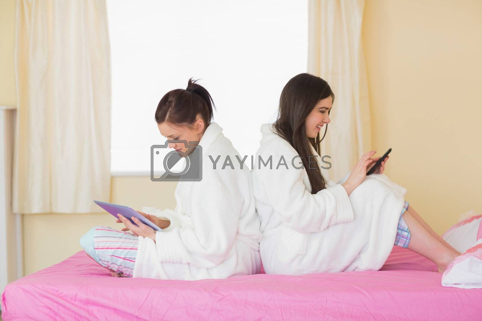 Two friends wearing bathrobes sitting back-to-back using smartphone and tablet by Wavebreakmedia