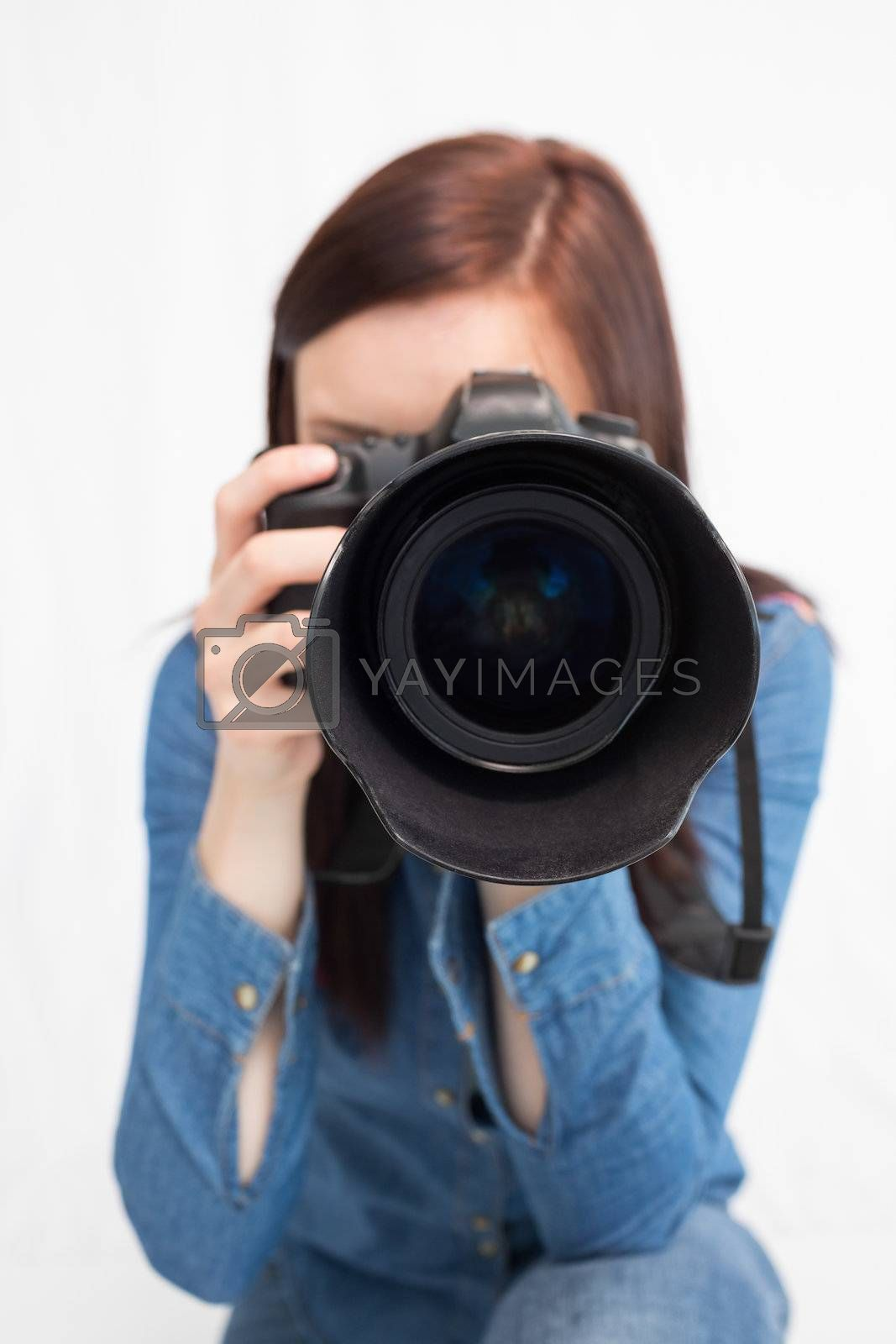 Casual young photographer taking picture of camera by Wavebreakmedia