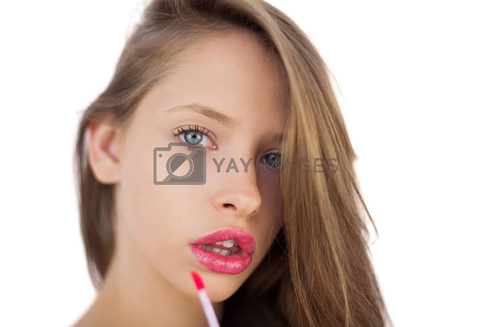 Serious brunette model applying pink gloss on her lips by Wavebreakmedia