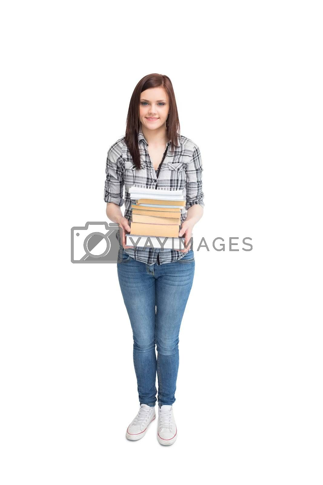 Smiling pretty student holding books by Wavebreakmedia